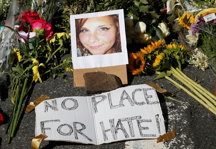A makeshift memorial of flowers and a photo of the victim of the car attack is on display at the attack site  in Charlottesville, Va., Sunday, Aug. 13, 2017.  (AP Photo/Steve Helber)