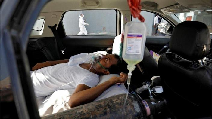 A patient with breathing problems lies inside a car while waiting to enter a COVID-19 hospital for treatment, amidst the spread of the coronavirus disease (COVID-19), in Ahmedabad, India, April 22,