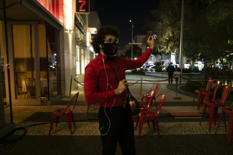 """An usher explains to the audience how to use an audio device to listen to the play """"7 Deadly Sins"""" on Lincoln Road in Miami Beach, Florida"""