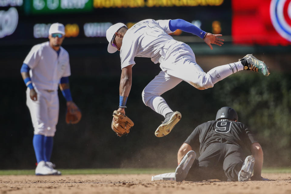 Chicago Cubs Tony Kemp, top, jumps over Washington Nationals' Brian Dozier after tagging him out at second base during the seventh inning of a baseball game Saturday, Aug. 24, 2019, in Chicago. (AP Photo/Kamil Krzaczynski)