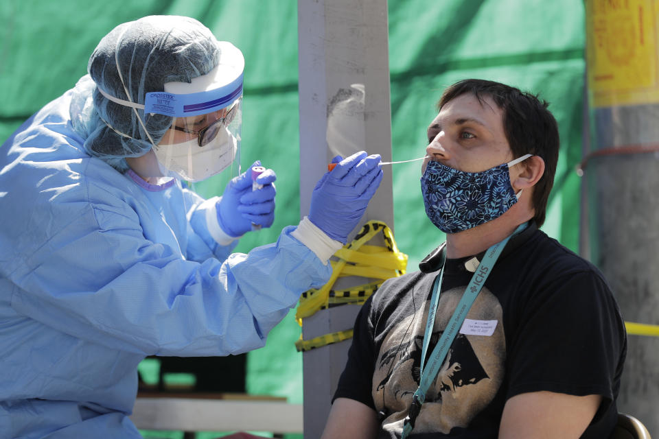 "FILE - In this May 16, 2020, file photo, Tina Nguyen, left, a nurse at the International Community Health Services clinic in Seattle's International District, takes a nose swab sample from David Carroll, an ICHS employee, during testing for the coronavirus in Seattle. At a cost of $120-130 per test and NHL Commissioner Gary Bettman's estimate the league will need 25,000-35,000 in total to get through the playoffs, the price tag he concedes is ""millions of dollars."" But regular testing is something players insisted on in the name of feeling safe to compete.(AP Photo/Ted S. Warren, File)"