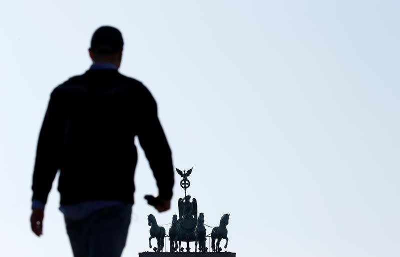 A person is silhouetted as he walks in front of the Brandenburg Gate during the outbreak of the coronavirus disease (COVID-19), in Berlin
