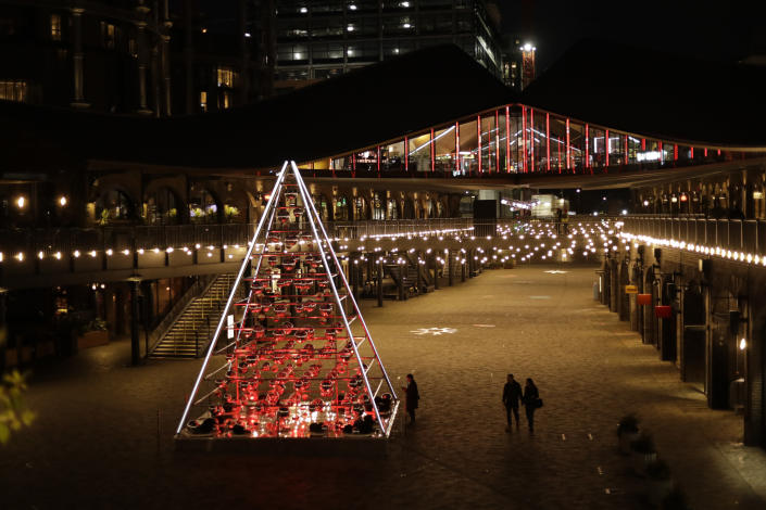 FILE - In this Monday, Nov. 23, 2020 file photo, people walk past the 'Terrarium Tree' in Coal Drops Yard, which forms part of the King's Cross neighbourhood of London's unconventional Christmas tree installations, during England's second coronavirus lockdown. Nations are struggling to reconcile cold medical advice with a holiday tradition that calls for big gatherings in often poorly ventilated rooms, where people chat, shout and sing together, providing an ideal conduit for a virus that has killed over 350,000 people in Europe so far. (AP Photo/Matt Dunham, FIle)