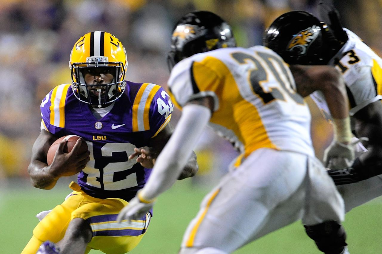 BATON ROUGE, LA - SEPTEMBER 29:  Jordan Dangerfield #20 and Telvion Clark #13 of the Towson Tigers pursue Michael Ford #42 of the LSU Tigers during a game at Tiger Stadium on September 29, 2012 in Baton Rouge, Louisiana.  LSU would win the game 38-22. (Photo by Stacy Revere/Getty Images)