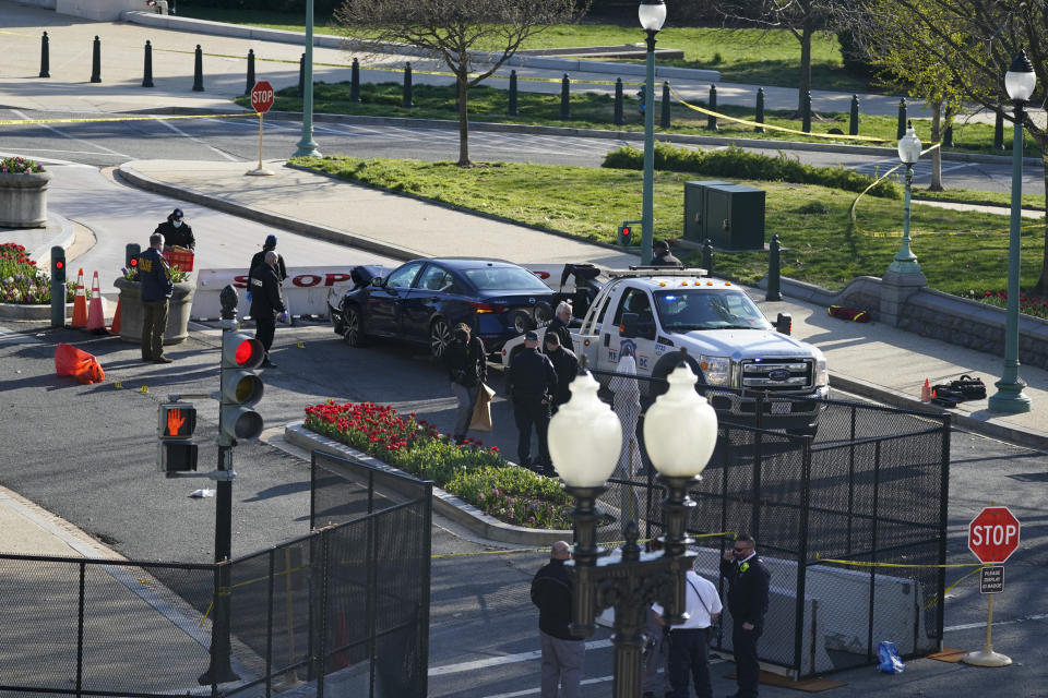 Authorities investigate the scene after a man rammed a car into two officers at the barricade on Capitol Hill in Washington, Friday, April 2, 2021. (AP Photo/Alex Brandon)