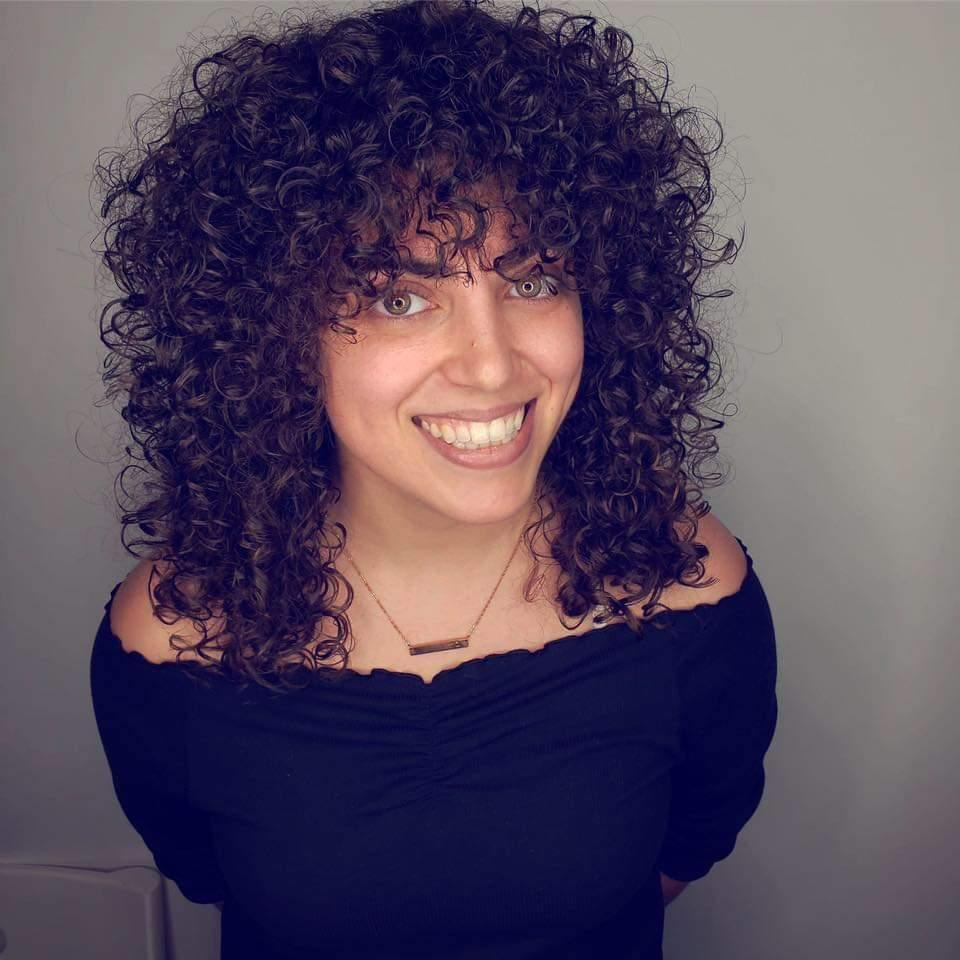 """Women in Detroit are all about embracing their natural texture and have been into the shag cut that's been popular for a few seasons now. Lauren Moser, curl specialist and owner of <a href=""""https://www.instagram.com/hairlabdetroit/"""" rel=""""nofollow noopener"""" target=""""_blank"""" data-ylk=""""slk:Hair Lab Detroit,"""" class=""""link rapid-noclick-resp"""">Hair Lab Detroit,</a> says that what makes the shag look more modern is working with your natural texture, which gives it that cool, lived-in look. While curly girls might be scared to go for bangs, Moser promises this cut works with all curl patterns. """"The defining feature of this cut is the heavy bangs and square layers that give this look its edge,"""" she says. """"For wavy curls and dense, tight S-curl types, be sure to request internal—or 'channel cut'—layers to be added in after the shape is cut to encourage weightlessness and texture throughout for ease of styling. For coily and kinky hair, this step is unnecessary since your curl type doesn't need help with volume."""""""