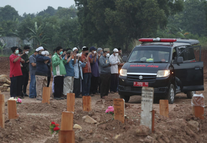Residents pray outside an ambulance carrying coffins of two COVID-19 victims before their burial at the special section of the Pedurenan cemetery in Bekasi, West Java, Indonesia, Friday, July 30, 2021. Indonesia surpassed the grim milestone of 100,000 official COVID-19 deaths on Wednesday, Aug. 4, 2021, as the country struggles with its worst pandemic year fueled by the delta variant, with growing concerns that the actual figure could be much higher with people also dying at home. (AP Photo/Achmad Ibrahim)