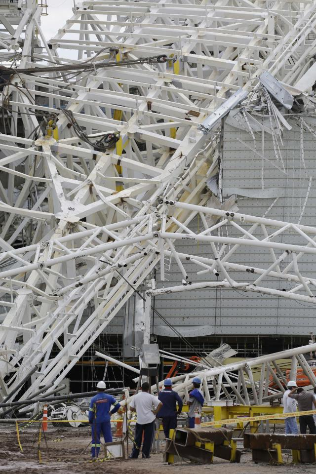 People stand near a metal structure that buckled on part of the Itaquerao Stadium in Sao Paulo, Brazil, Wednesday, Nov. 27, 2013. Part of the stadium that will host the 2014 World Cup opener in Brazil collapsed on Wednesday, causing significant damage and killing three people, authorities said. (AP Photo/Nelson Antoine)