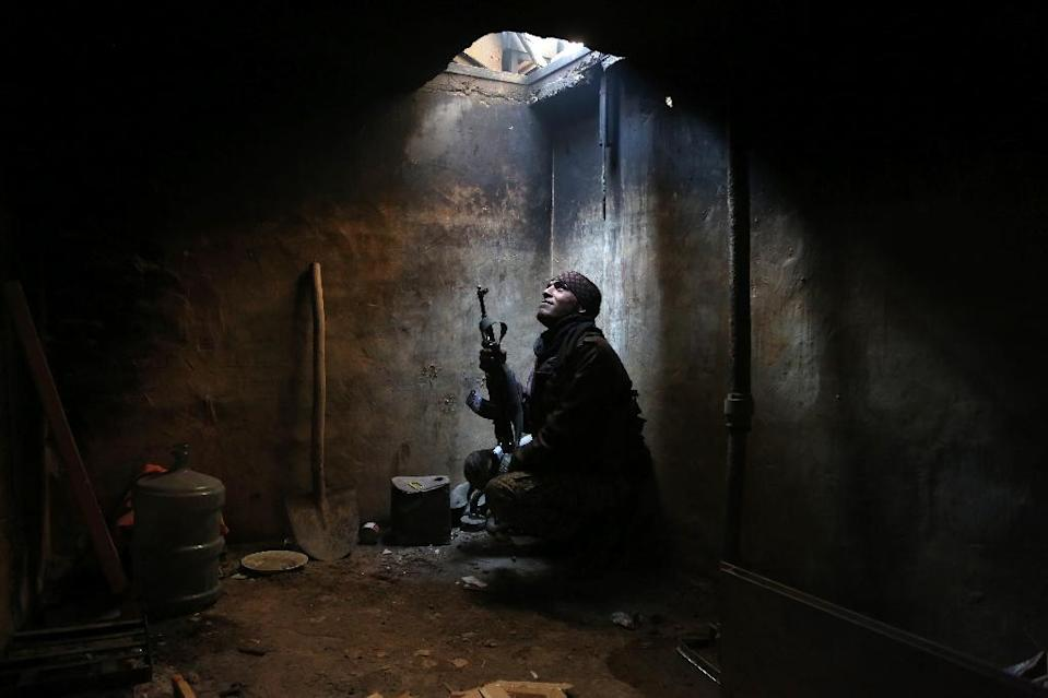 A Syrian rebel looks up from his hiding spot in the rebel-controlled area of Arbeen, on the outskirts of Damascus (AFP Photo/Amer Almohibany)