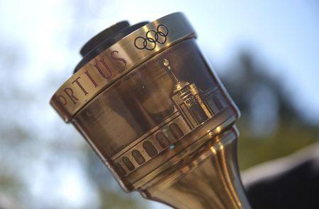The Olympic torch is shown with a depiction of the Los Angeles Coliseum prior to a news conference to annouce the city's final approval to bid for the 2024 Olympic Games, in Los Angeles