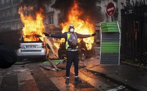 Protesters clashes with riot police on Foch avenue next to the Place de l'Etoile, setting cars ablaze during a Yellow Vest protest on December 1, 2018 in Paris, France - Credit: Etienne De Malglaive/Getty Images Contributor