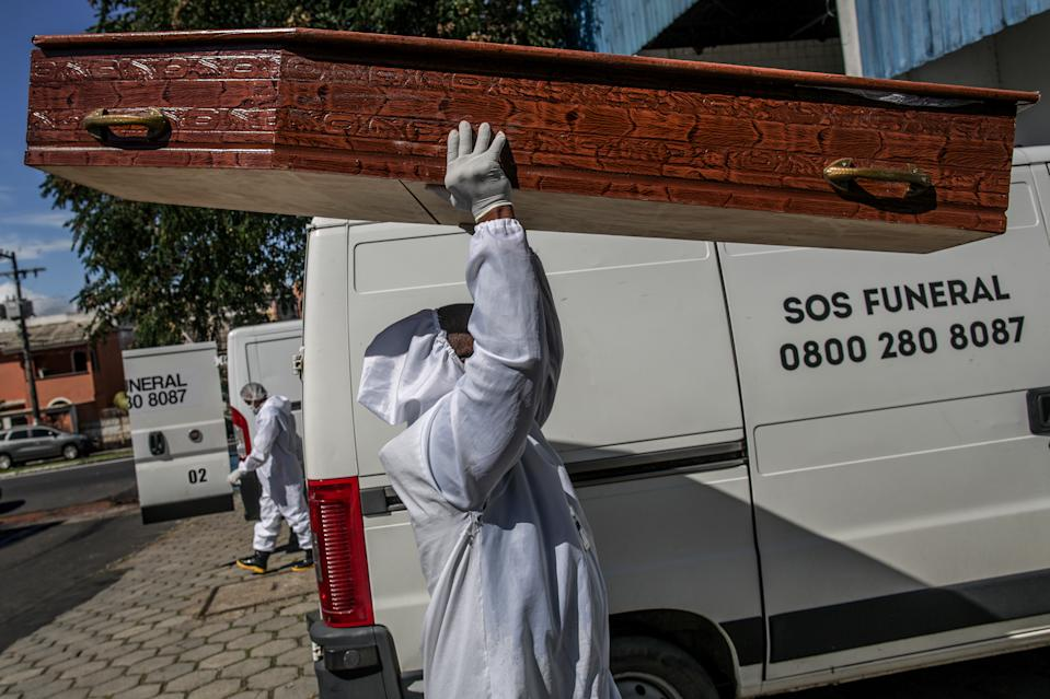 A funeral employee carries a coffin in Manaus.