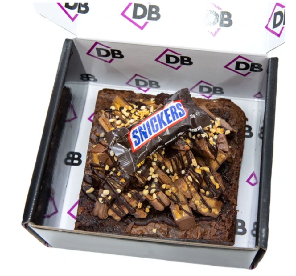 A giant brownie topped with Snickers bars and TimTams