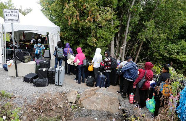 A line of asylum seekers who identified themselves as from Haiti wait to enter into Canada from Roxham Road in Champlain, N.Y. on Aug. 7, 2017.