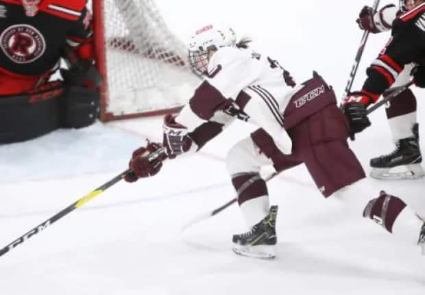 In this file photo, a member of the Saint Mary's University women's hockey team is shown reaching for a puck against University of New Brunswick. (Nick Pearce - image credit)