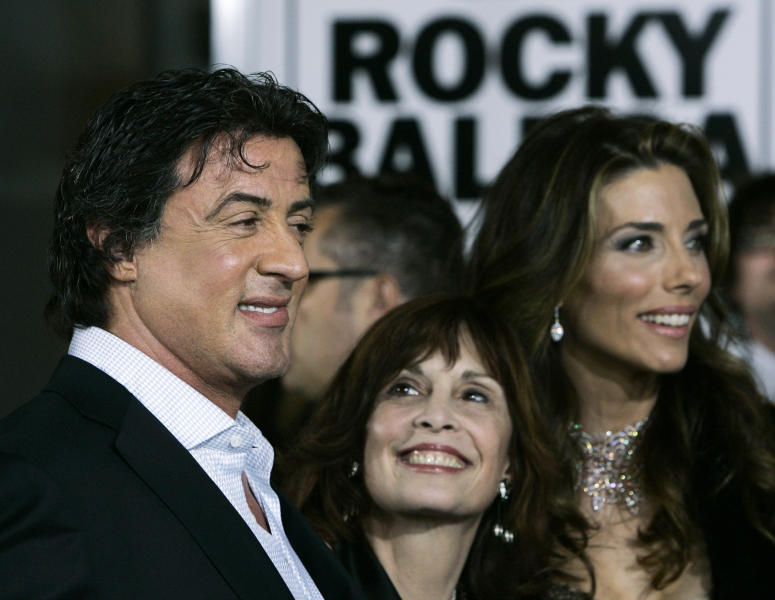 "FILE – In this Dec. 13, 2006, file photo, actor and screenwriter Sylvester Stallone, left, poses with actress Talia Shire, center, who played his wife in the ""Rocky"" movies, and his wife Jennifer Flavin Stallone, right, at the premiere of the movie ""Rocky Balboa"" in the Hollywood section of Los Angeles. Four decades after the Nov. 21, 1976, premiere of ""Rocky,"" the movie's reach is international, and the title character's underdog tale of determination, grit and sleepy-eyed charm still resonates with fans. (AP Photo/Kevork Djansezian, File)"