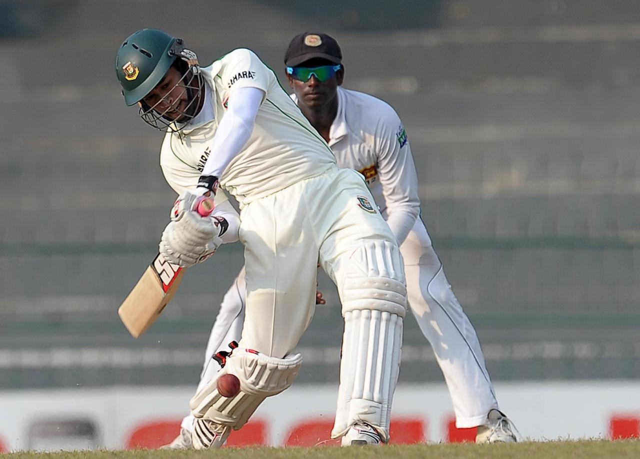 Bangladeshi captain Mushfiqur Rahim (L) plays a shot as Sri Lankan captain Angelo Mathews look on during the third day of their second Test match between Sri Lanka and Bangladesh at the R. Premadasa Cricket Stadium in Colombo on March 18, 2013. AFP PHOTO/ LAKRUWAN WANNIARACHCHI