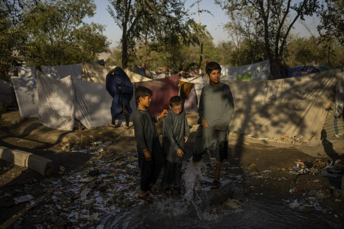 Afghan children wash their feet in a fountain at an internally displaced persons camp in Kabul, Afghanistan, Monday, Sept. 13, 2021. (AP Photo/Bernat Armangue)