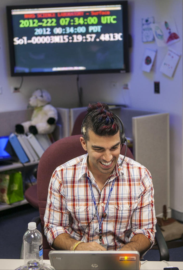 """In this photo taken Thursday, Aug. 9, 2012, Bobak Ferdowsi, a flight director for the Mars rover Curiosity, works at his computer at the Surface Mission Support Area, at NASA's JPL in Pasadena, Calif. Known to the Twitterverse and the president of the United States as """"Mohawk Guy,"""" Bobak Ferdowski could be the changing face of NASA and all of geekdom. (AP Photo/Damian Dovarganes)"""