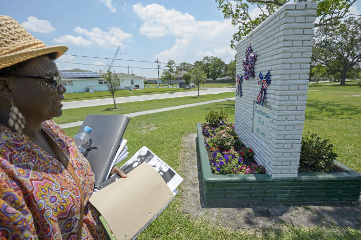 FILE - Carrie Mingo Douglas, a member of the Pontchartrain Park neighborhood association and chair of the association's historic district committee, walks around the historic sign of the housing development that she helps maintain in New Orleans, in a Friday, June 8, 2018 file photo. Pontchartrain Park, the first subdivision built for middle- and upper-class Black residents of New Orleans is now on the National Register of Historic Places. (Max Becherer /The Advocate via AP, File)