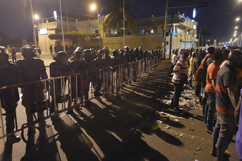 Anti-riot policemen (L) block the road against opposition supporters (R) keeping an all-night vigil to press for constitutional reform, during anti-government protests led by a coalition of opposition parties in Lome, on September 7, 2017 (AFP Photo/PIUS UTOMI EKPEI)