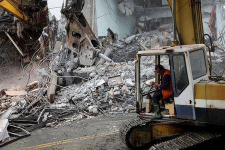 An excavator demolishes collapsed Marshal hotel after an earthquake hit Hualien, Taiwan February 9, 2018. REUTERS/TyroneSiu