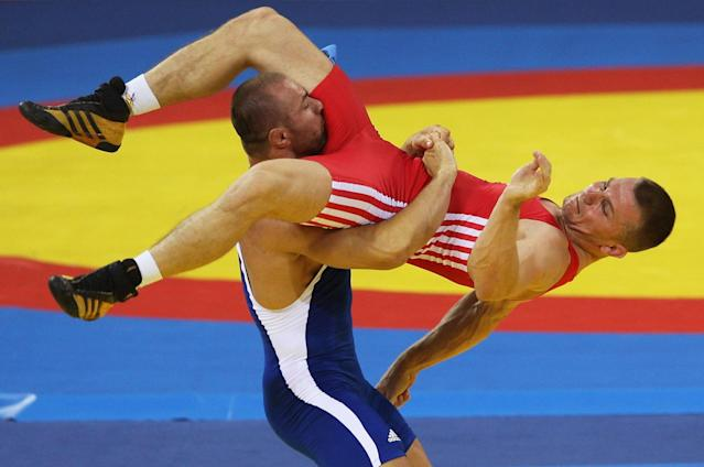 BEIJING - AUGUST 14: Marek Svec (red) of the Czech Republic is thrown by Aslanbek Khustov (blue) of the Russian Federation in the Men's Greco-Roman 96kg semi final bout at the China Agriculture University Gymnasium during Day 6 of the Beijing 2008 Olympic Games on August 14, 2008 in Beijing, China. (Photo by Ezra Shaw/Getty Images)