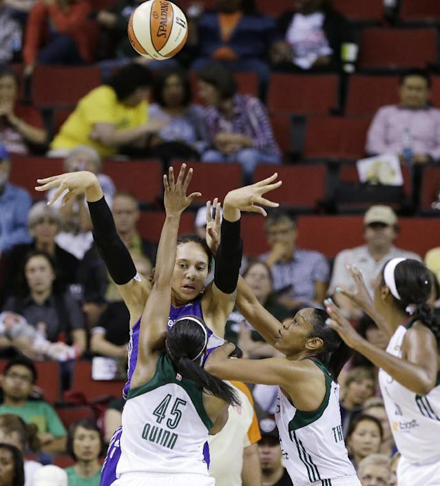 Phoenix Mercury's Brittney Griner, top, gets a pass off while defended by Seattle Storm's Noelle Quinn (45) and Tina Thompson in the first half of a WNBA basketball game on Thursday, Aug. 1, 2013, in Seattle. (AP Photo/Elaine Thompson)