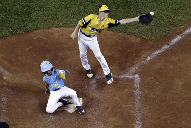 Wailuku, Hawaii's Marley Sebastian, left, scores on a wild pitch as the throw from South Riding, Va., catcher Noah Culpepper gets past pitcher Chase Obstgarten, allowing a second run to score during the third inning of a baseball game at the Little League World Series in South Williamsport, Pa., Wednesday, Aug. 21, 2019. Hawaii won 12-9. (AP Photo/Gene J. Puskar)