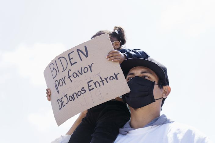 A migrant child holds a sign that reads in Spanish