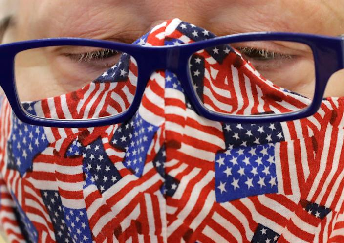 Donning a patriotic mask, Dianna Grindstaff-Abbott assists citizens in the voting process at the former Shopko building Tuesday, Nov. 3, 2020, in Neenah, Wis.