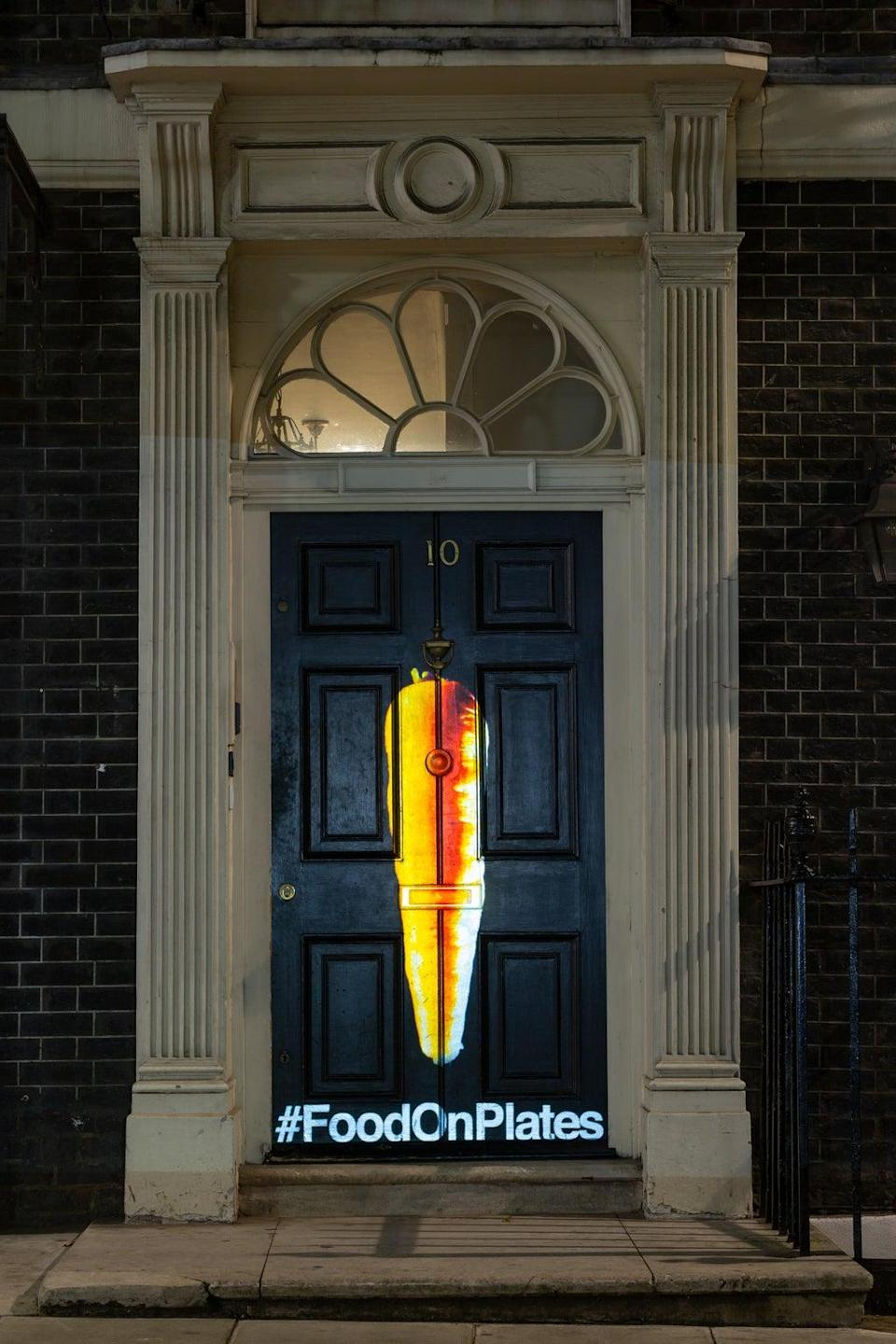 A lone carrot projected onto a front door in Westminster (FareShare)