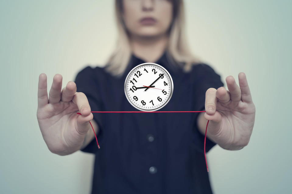 Woman's hands hold a wall clock balanced on a thread