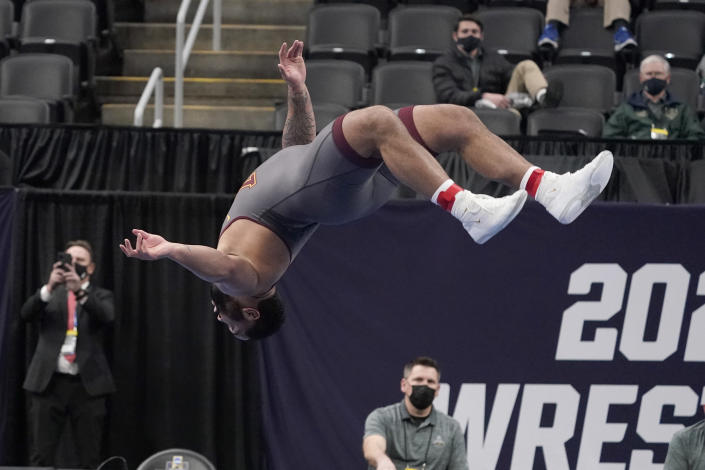 FILE - Minnesota's Gable Steveson does a backflip to celebrate after defeating Michigan's Mason Parris in their 285-pound match in the finals of the NCAA wrestling championships in St. Louis, in this Saturday, March 20, 2021, file photo. The charismatic 21-year-old hopes a successful run at the Games launches him into a WWE career like his mentor, Brock Lesnar, and an acting career like former WWE star Dwayne 'The Rock' Johnson. (AP Photo/Jeff Roberson, File)