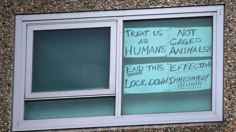 A sign in the window of one of the locked-down units reads: Treat as as humans, not as caged animals""
