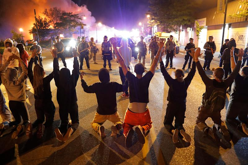 <strong>Demonstrators kneel before police inMinneapolis in the early hours of Saturday morning.</strong> (Photo: ASSOCIATED PRESS)