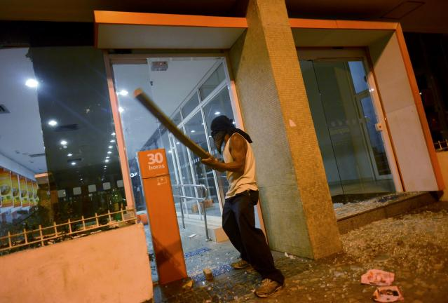A masked protester breaks the windows of a bank during a demonstration against the public spending for the 2014 World Cup, in Rio de Janeiro June 15, 2014. Police blocked the streets to keep demonstrators from reaching Maracana soccer stadium as Argentina played Bosnia and Herzegovina for Group F. REUTERS/Stringer/Brazil (BRAZIL - Tags: SPORT SOCCER WORLD CUP CIVIL UNREST POLITICS TPX IMAGES OF THE DAY)
