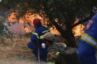 Firefighters try to extinguish a wildfire near Olympia town, western Greece, Thursday, Aug. 5, 2021. Wildfires rekindled outside Athens and forced more evacuations around southern Greece Thursday as weather conditions worsened and firefighters in a round-the-clock battle stopped the flames just outside the birthplace of the ancient Olympics. (Giannis Spyrounis/ilialive.gr via AP)