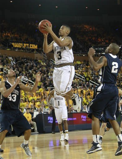 Michigan guard Trey Burke (3) goes for two points between Penn State forward Ross Travis (43) and guard D.J. Newbill (2) during the second half of an NCAA college basketball game at Crisler Center in Ann Arbor, Mich., Sunday, Feb. 17, 2013. (AP Photo/Carlos Osorio)