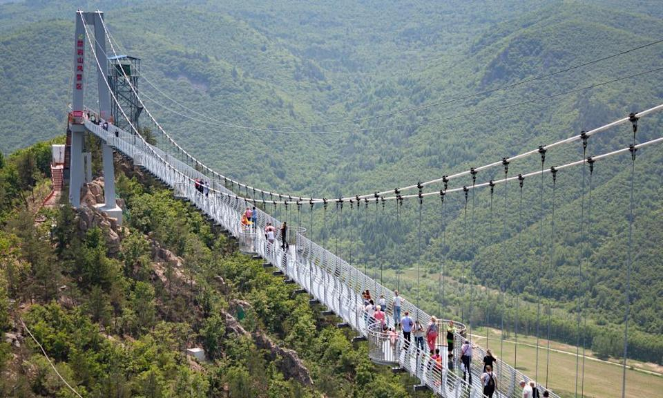 Tourists walking across the glass-bottomed suspension bridge in Longjing, China, in 2019.