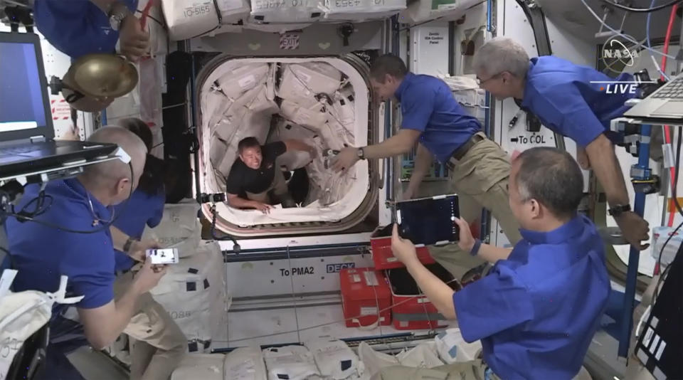This image provided by NASA, astronauts from SpaceX begin to enter the International Space Station after the Dragon capsule successfully docked on Saturday, April 24, 2021. The recycled SpaceX capsule carrying four astronauts has arrived at the International Space Station, a day after launching from Florida. (NASA via AP)