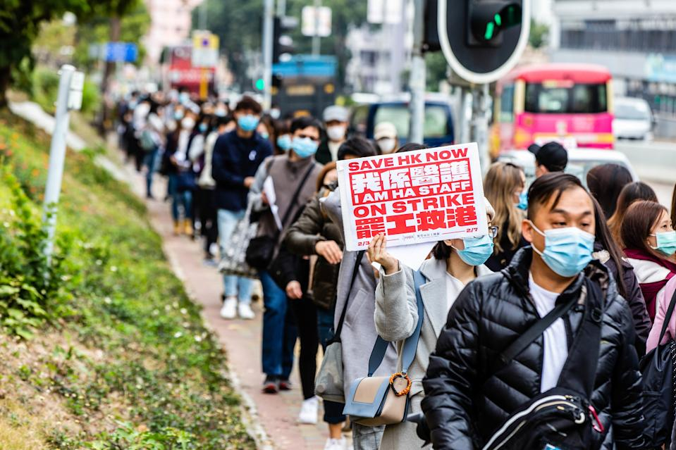 HONG KONG, CHINA - 2020/02/04: Hospital workers march while wearing surgical masks during the strike in Hong Kong. Hong Kong hospital staff strike to demand closure of China border amid coronavirus fears. (Photo by Willie Siau/SOPA Images/LightRocket via Getty Images)
