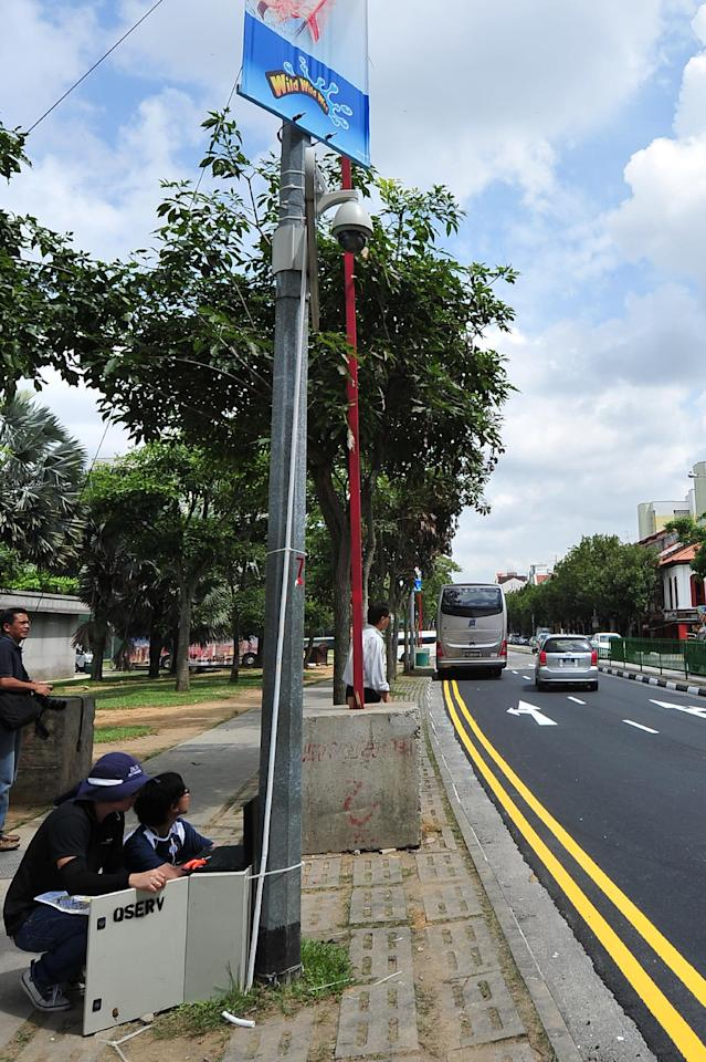 (131211) -- SINGAPORE, Dec. 11, 2013 (Xinhua) -- Workers install a closed-circuit television camera along Singapore's Race Course Road, Dec. 11, 2013. The situation in Singapore's Little India continues to be peaceful. (Xinhua/Then Chih Wey)