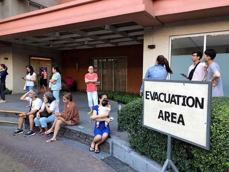 Residents sit outside after being evacuated from the condominium building after an earthquake in Makati City, Philippines, April 22, 2019. REUTERS/Martin Petty
