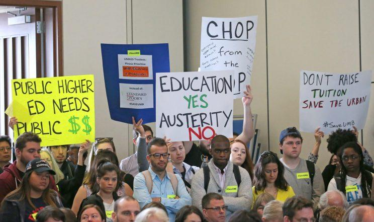 Demonstrators hold signs against tuition increases and budget cuts at the UMass Board of Trustees meeting at the UMass Boston campus on Apr. 12, 2017. (Photo: David L. Ryan/The Boston Globe via Getty Images)