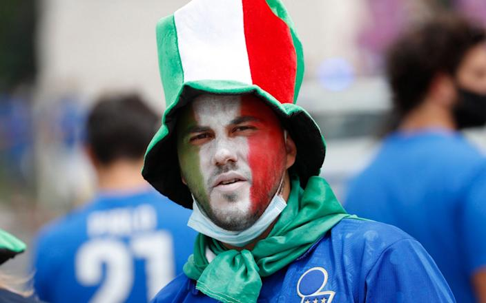 Fans gather for Italy v Wales - Rome, Italy- June 20, 2021 Fan with an Italy flag painted on his face before the match - REUTERS