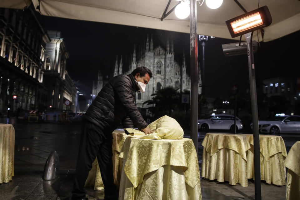 A waiter clears tables at a cafe restaurant in front of the gothic cathedral in Milan, Italy, Thursday, Oct. 22, 2020. Authorities in regions including Italy's three largest cities have imposed curfews in a bid to slow the spread of COVID-19, as many of the cases in Lombardy's surging outbreak have occurred in Milan. On Thursday, an overnight curfew takes effect in the city, known for its lively night-time bar scene, and the rest of the region, as authorities try to slow the spread of the contagion. (AP Photo/Luca Bruno)