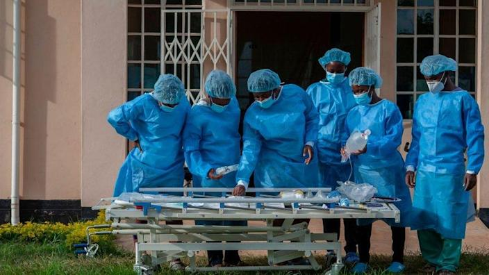 People in personal protective equipment are seen at a lodging building readying for their turn to go and work inside the main COVID-19 treatment centre at Kamuzu Central Hospital in Lilongwe, Malawi, on January 18, 2021.