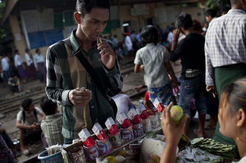 In this Aug. 13, 2013 photo, a man buys a cigarette from a street vendor at a railway station platform in the suburbs of Yangon, Myanmar. As some of the world's biggest companies trumpet their arrival in Asia's hottest frontier market, the tobacco industry has a different strategy: It's slipping into Myanmar without fanfare. In this impoverished nation of 60 million people emerging from a half-century of isolation and brutal military rule two years ago, awareness about the health hazards is low, tobacco controls are weakly enforced, and the anti-smoking lobby is effectively a one man act. (AP Photo/Gemunu Amarasinghe)