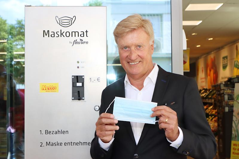 """HAMBURG, GERMANY - MAY 28: German politician Ole von Beust presents the first protective face mask vendor for supermarket chain Netto during the Coronavirus crisis on May 28, 2020 in Steilshoop, Hamburg, Germany. The self-service vendor called """"Maskomat"""" by Flavura is placed in front of the grocery store to provide customers with single-use protective face masks for one Euro each. (Photo by Tristar Media/Getty Images)"""